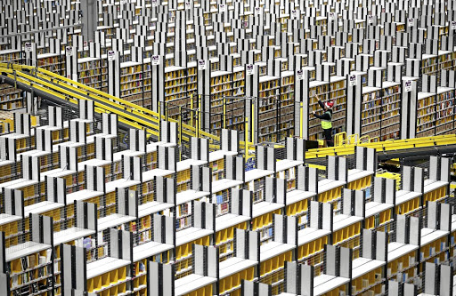 Staff collect items which will be packaged and dispatched from one of the UK's largest Amazon warehouses, in Dunfermline, Fife. There are extra shipment charges on some online deals that international retailers often don't bother to disclose. Picture: GETTY IMAGES