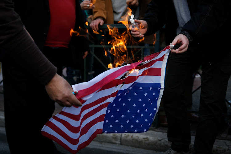 Protesters burn an US flag during a demonstration outside the US embassy against air strikes carried out in Syria, in Athens, Greece, April 14, 2018.
