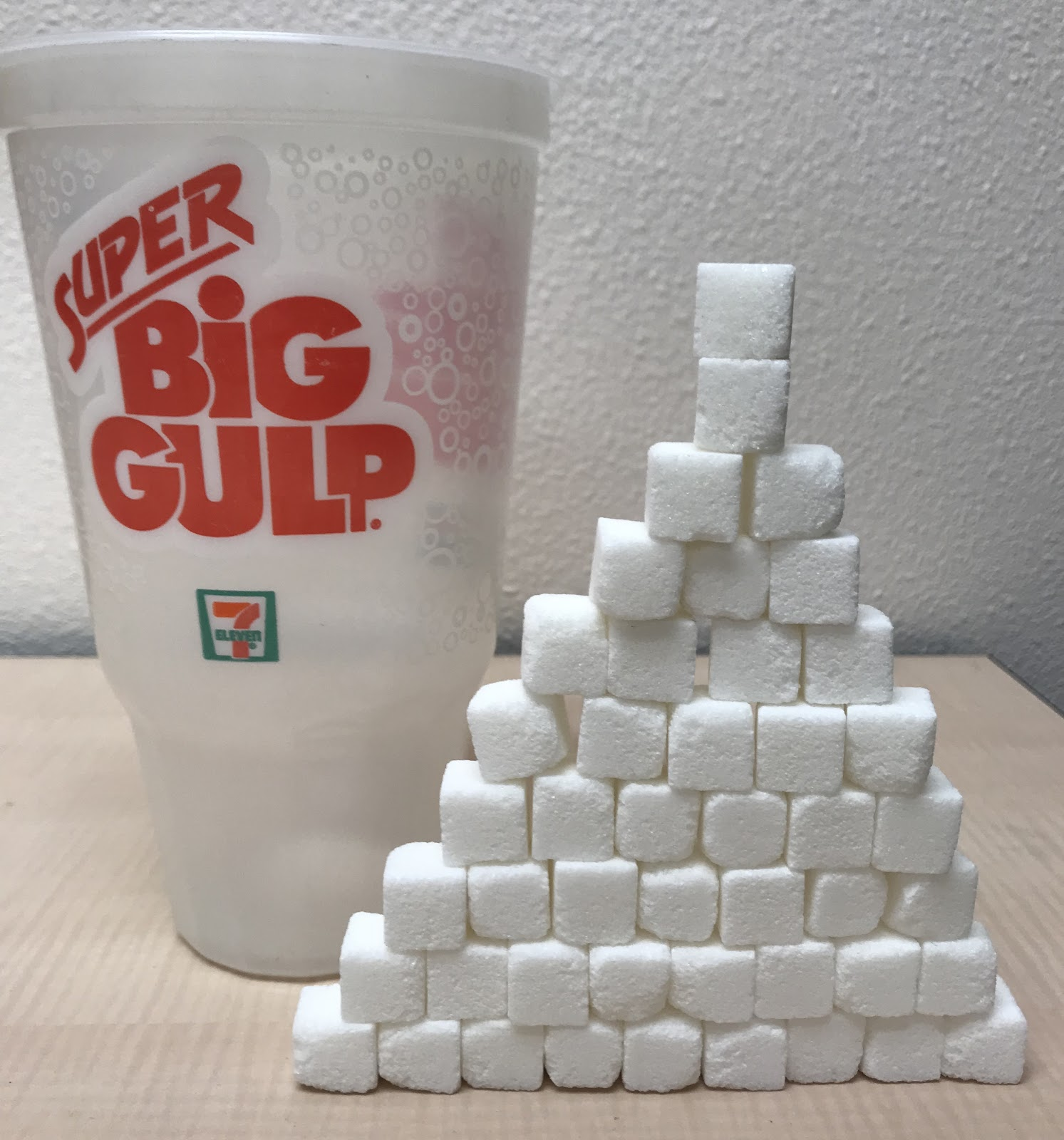 Forty six sugar cubes stacked next to a big gulp to illustrate the 46 teaspoons of sugar that the soda contains.