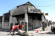 Metal collectors get into businesses after shops  were looted and  burnt on Jules Street, Malvern, in Johannesburg last Sunday. /Thulani Mbele