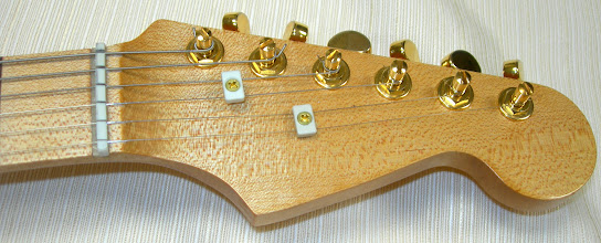Photo: Tusq nut and string tees. Grover locking tuners. Also note nut slot filler, from original attempt to produce a Corian compensated nut. (The top of the nut has since been lowered and comfortably shaped.)