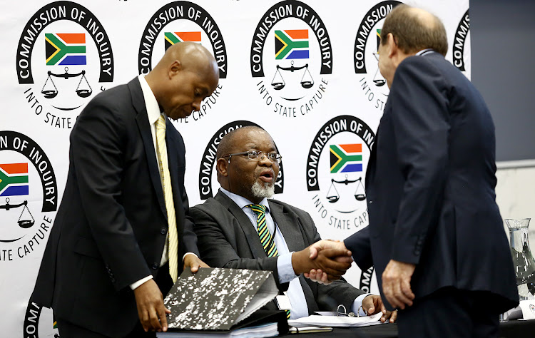ANC chair Gwede Mantashe shakes hands with head of the state capture investigation, advocate Paul Pretorius as advocate Phillip Mokoena looks at a file before his testimony.