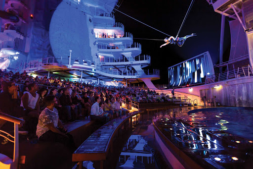 harmony-of-seas-aquatheater-show.jpg - Audience members look up at a performer flying above water in the AquaTheater on Harmony of the Seas.