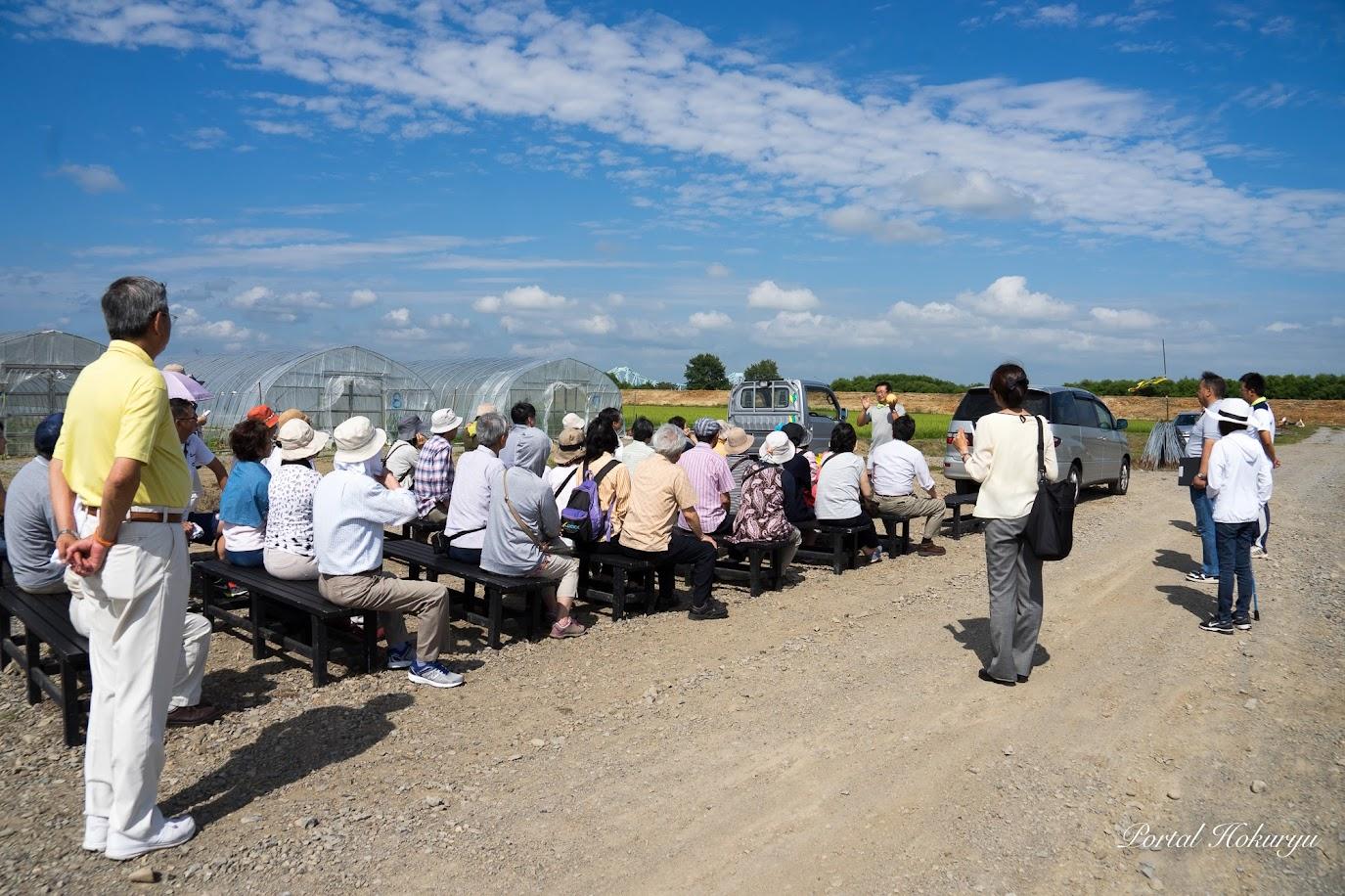 青空の下、北竜町のメロン栽培のお話しに耳を傾けます