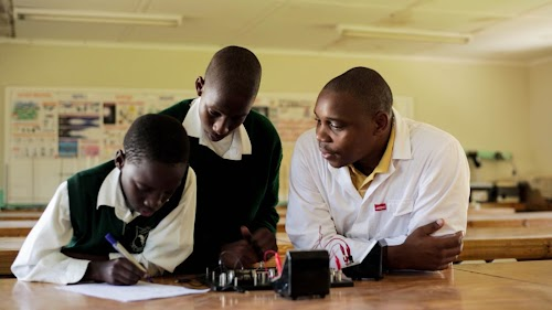 Sakhiwe and Bonkhe in the classroom with their teacher, Mr. Sithole.
