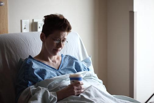 woman on hospital bed holding plastic bottle