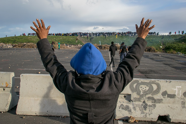A Hermanus resident holds up his hands in an attempt to stop protesters from throwing rocks at police on July 13 2018