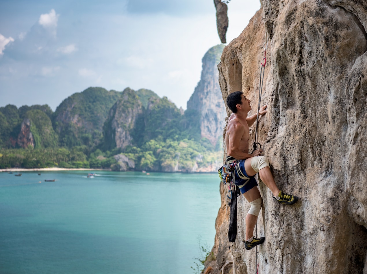 Man rock climbing at Railay Beach, Tonsai, Krabi travel guide