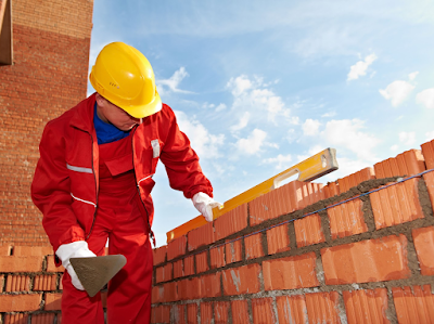 a man with a hard hat on using a level to measure the level of bricks