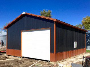 Navy and brown pole barn with white door