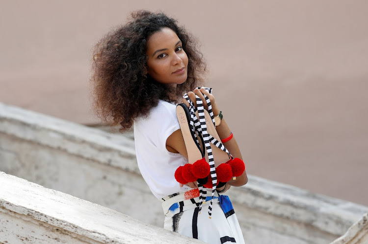"Italian-Haitian fashion designer Stella Jean shows the shoes she designed as she poses for a picture along the Spanish Steps ahead of the ""We Are Made In Italy"" Black Lives Matter fashion show at Milan Fashion Week."