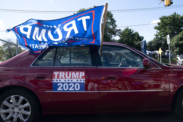 Supporters of US President Donald Trump drive by a rally outside Walter Reed National Military Medical Center in Bethesda, Maryland. Picture: Stefani Reynolds/Bloomberg