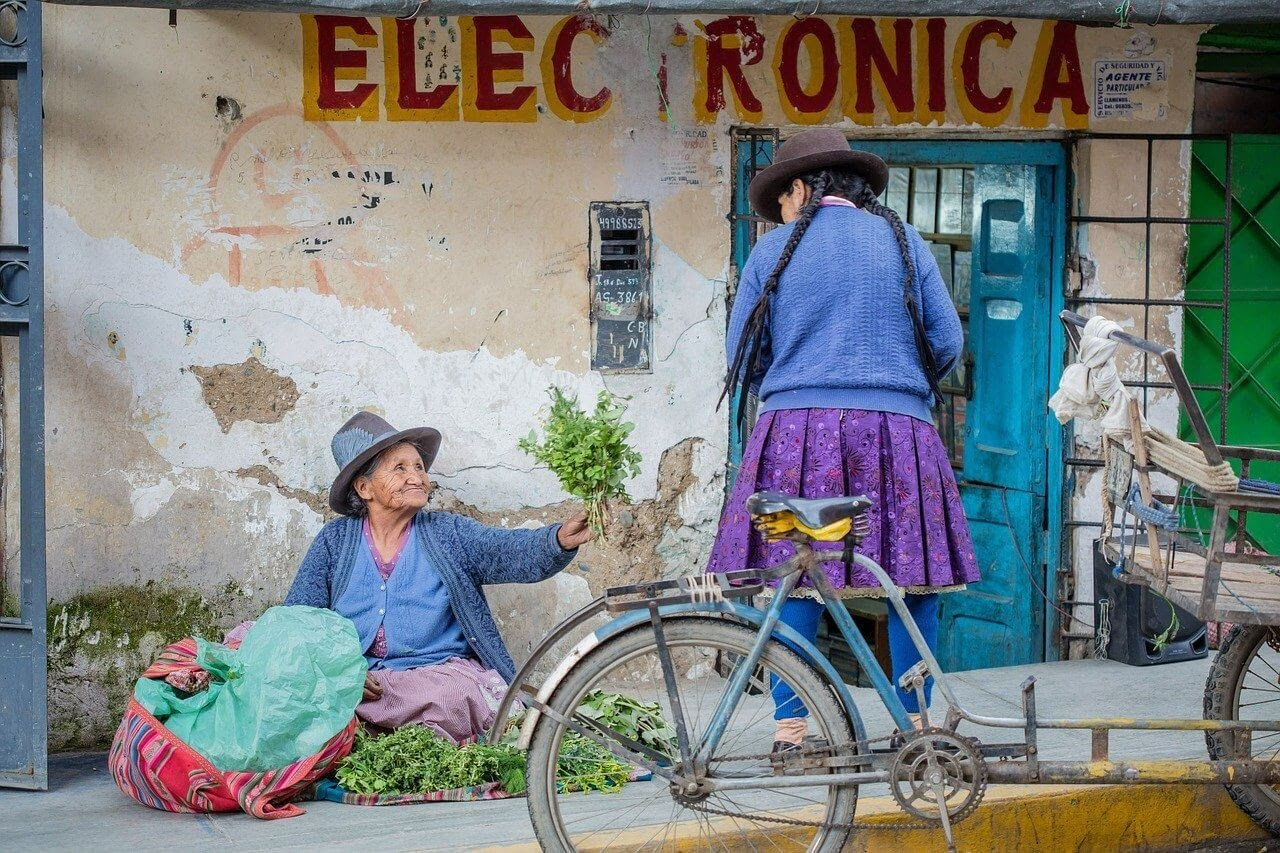 peruvian ladies sitting on a street in peru