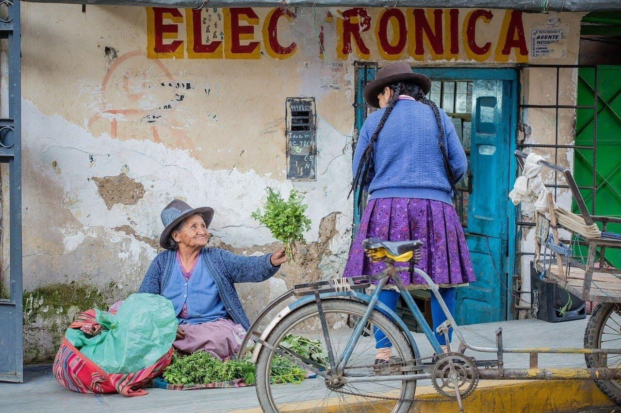 peruvian ladies sitting on a street in peru