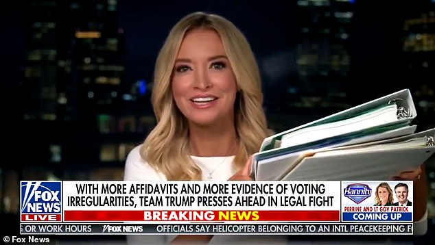 A screenshot of Kayleigh McEnany on FoxNews holding two white binders, wearing a white shirt, and just being very very white in general.