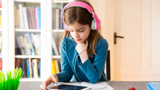 image of young girl with headphones on reading