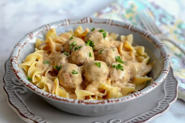 A Bowl Of Slow Cooker Swedish Meatballs With Egg Noodles.