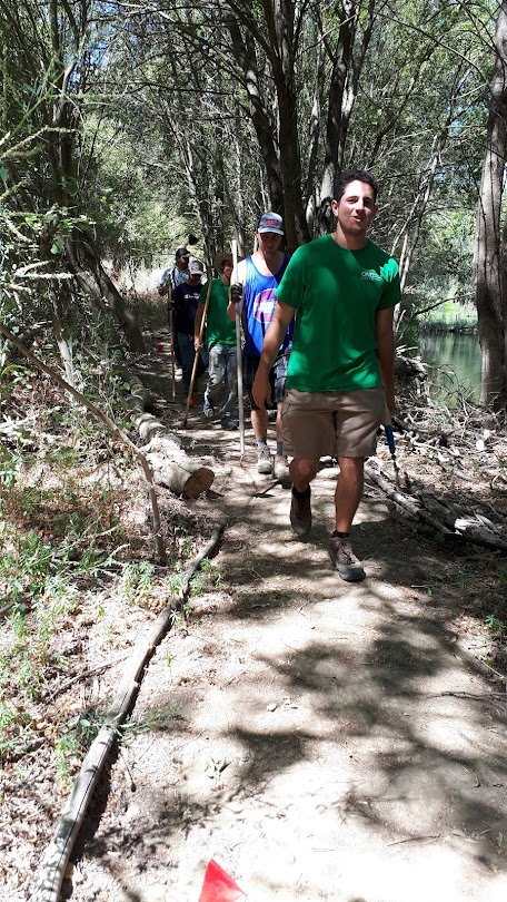 This image shows interns carrying tools along a wooded trail.