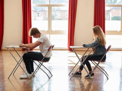 two students writing in an exam room
