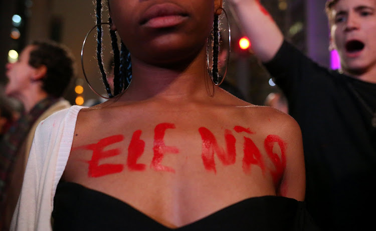 A demonstrator displays the words 'Not him' on her body in reference to Jair Bolsonaro, a far-right lawmaker and presidential candidate, in Sao Paulo.