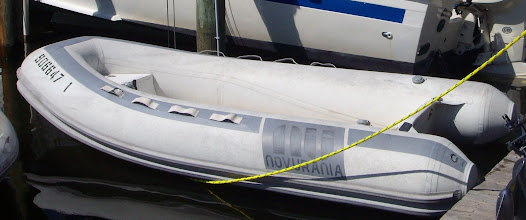 "Photo: Close up of Troubadour's Inflated dinghy - notice ""double"" rub rail ... inflation ports - one on each side pontoon, one at the inside of the port bow pontoon...d-rings on aft end of pontoons ..."