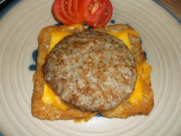 Place sausage patty on top of the hash browns and cheese; place tomato slices...