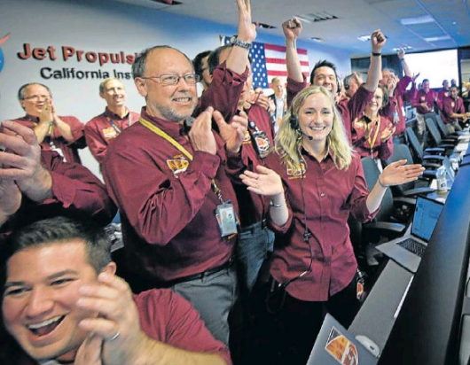 Nasa JPL InSight principal investigator Bruce Banerdt, centre, and team members celebrate the first image of Mars from the InSight lander at Nasa's laboratory in California.