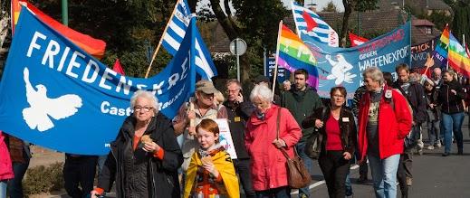 Viele Menschen, alt und jung, mit Friedensfahnen und Transparenten.