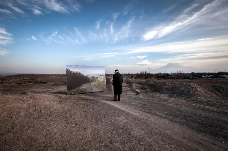Photo d'un vieil homme dans un paysage désertique qui se tient devant un miroir dans lequel il observe son reflet