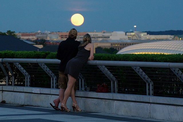 A couple glances at the full moon from the Rooftop Terrace at the Kennedy Center. Photo: philliefan99 / flickr