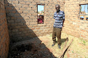 Landlord Reginald Leshapa in front of a shallow grave where Katlego Mokwana's body was found. / PETER RAMOTHWALA