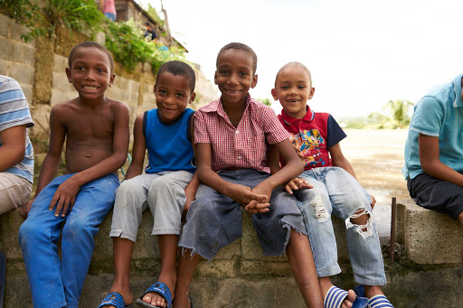 DR-Local-Kids-Sitting-on-Wall.jpg - Impact travel brings you into communities in the Dominican Republic.