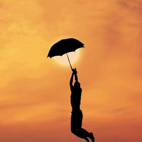 hanging on sun by Adrian  Limani - People Fine Art ( sunset, silhouette, umbrella, sun )