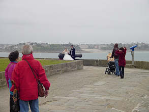 Photo: Wedding photos at historic sites seem quite popular in France. In this case, however, the couple seemed not quite as bemused as the bystanders as they worked to keep their composure and appearance on a gusty and drizzly day.