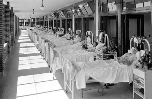 Personas enfermas recostadas en camillas del sanatorio