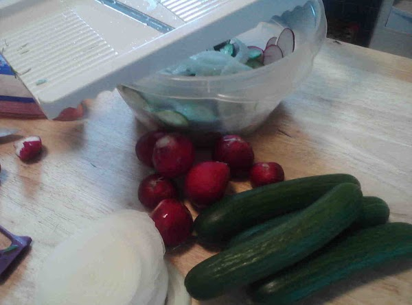 Using a mandeline slice radishes, cucumbers, and onions. Toss in bowl with cheese crumbles.