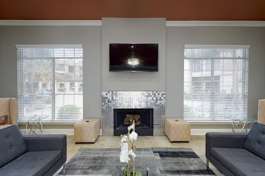 Community clubhouse with gray couches and fireplace