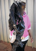 The mother of the boy who survived a necklacing in Daveyton holds his scorched clothes.
