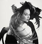 modieuze vrouw met hoed waarop 2 kippen met lange staarten