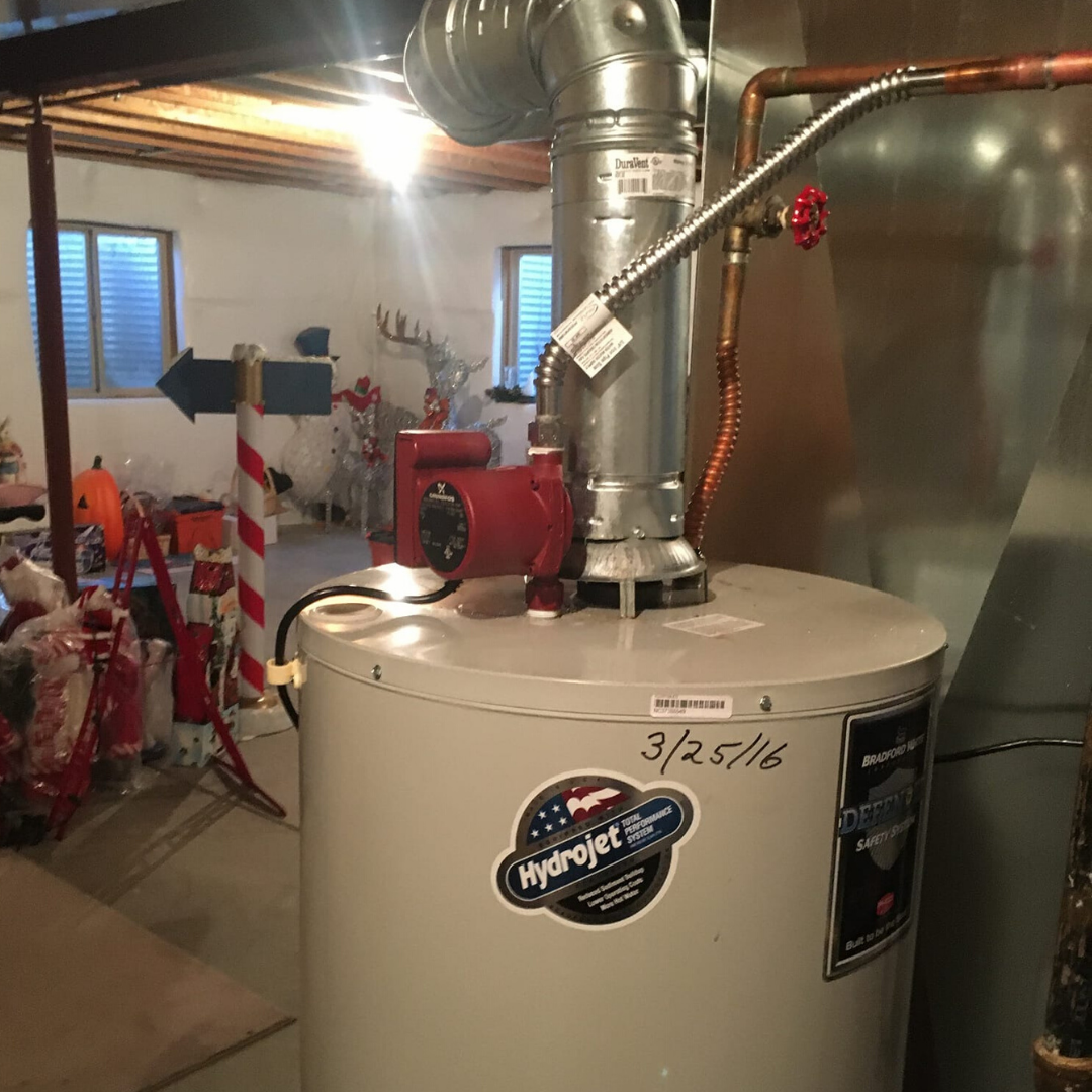 red and black Grundfos hot water recirculation system installed on top of a tank water heater in a basement
