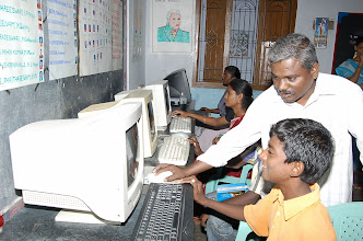 Photo: A young rural boy enjoys working on the computer,who is assisted by our project volunteer