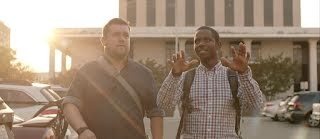 Founders, Bernard Worthy and Justin Straight, stand side by side in a parking lot looking up.