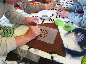 Photo: Lewie needlefelts the boat registration numbers and letters onto the sail.