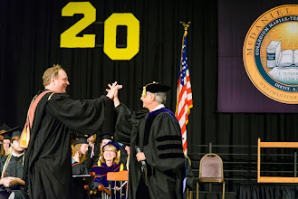"Photo: Cinema Professor Jonathan Slade hi-fives with Provost Tom Zirpoli. Slade was the ""secret"" faculty speaker at Friday's Honors Convocation."