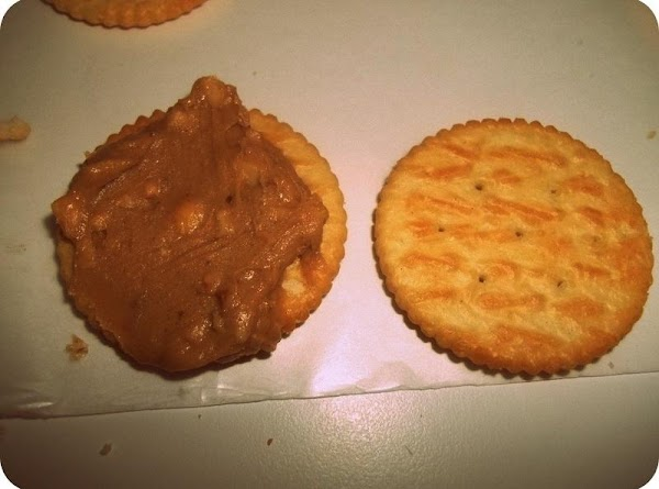 Spread about a teaspoon of peanut butter on 1 sleeve of crackers.
