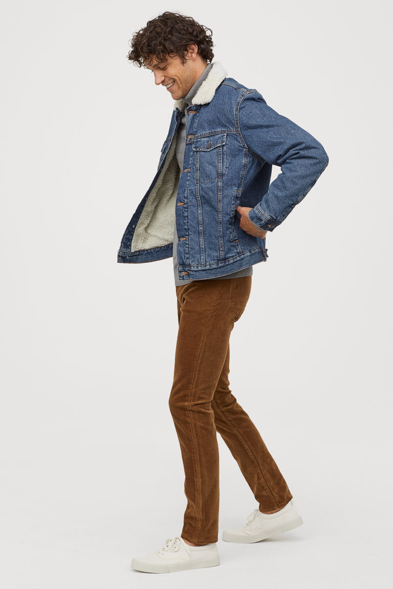 Individual posing while wearing a denim jacket and brown pants