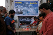 People light candles during a prayer service for those who died on Mount Everest during expeditions as they celebrate Everest Day in Kolkata, India