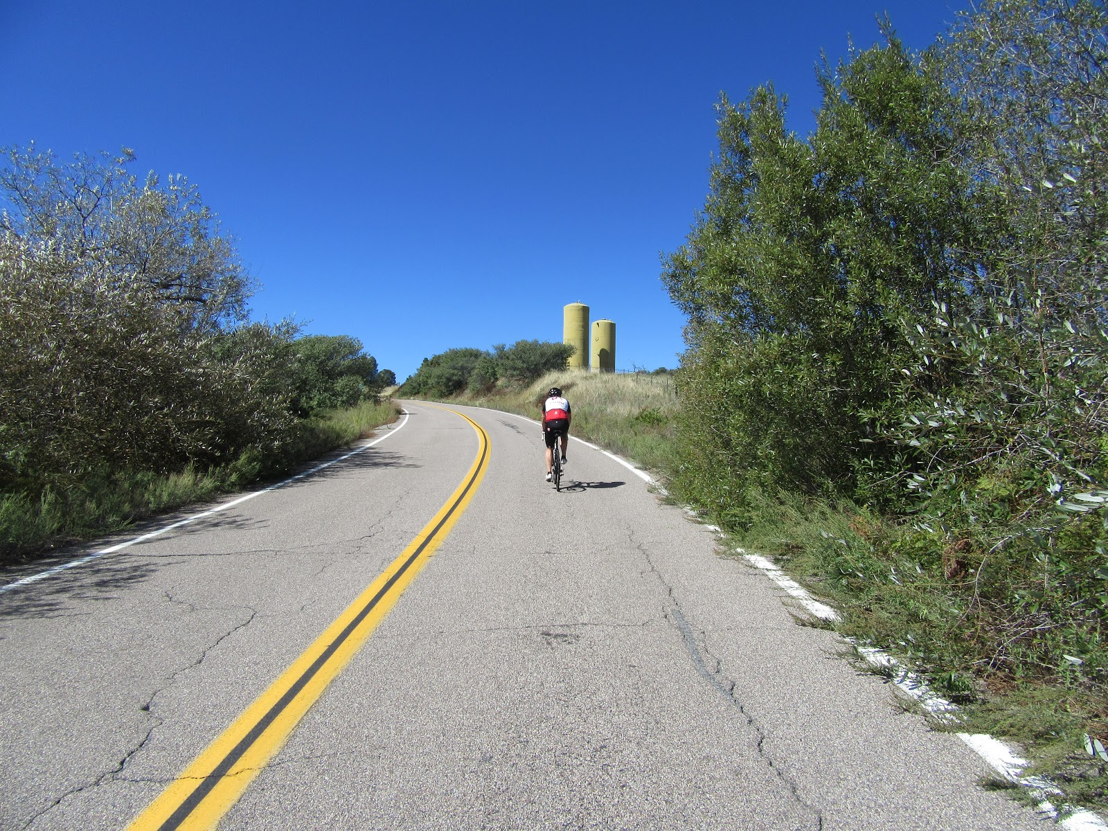 Riding East Grade Road by bike - cyclist and silos