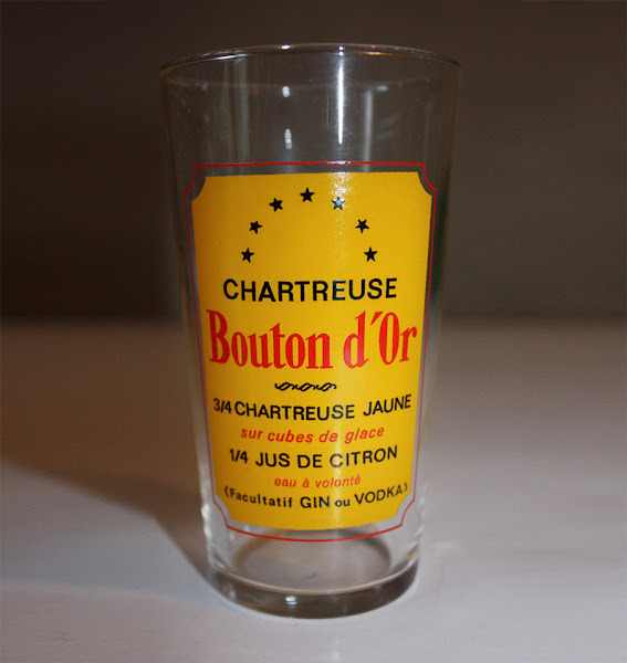 Photo: Verre sur lequel figure la recette du Bouton d'Or, un mélange de Chartreuse Jaune et de jus de citron.