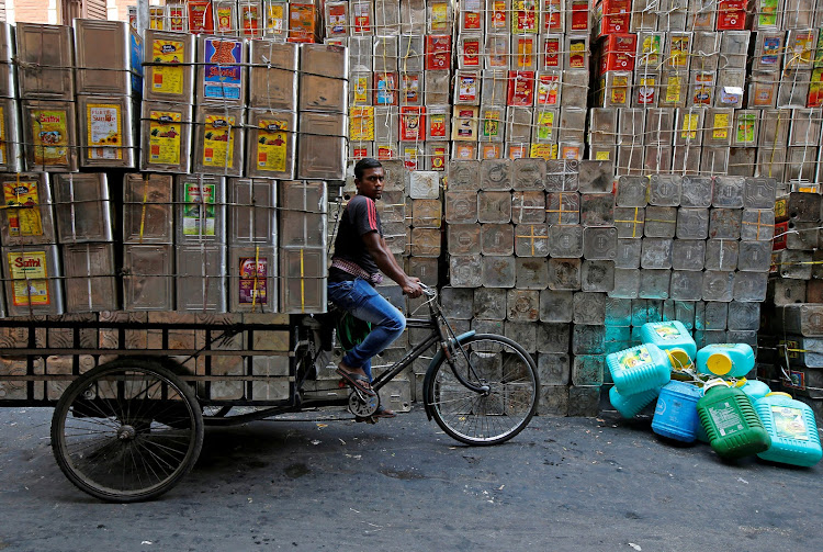 A man pedals a tricycle loaded with empty cooking oil containers in Kolkata, India.